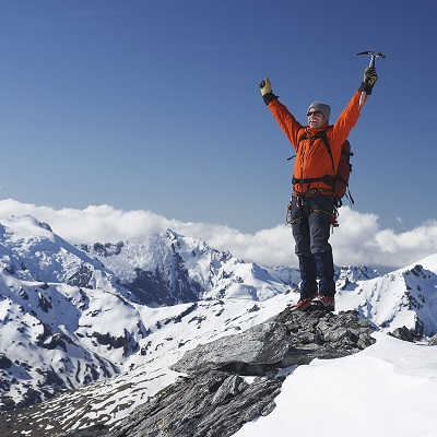 Excited Mountaineer Standing on Apex